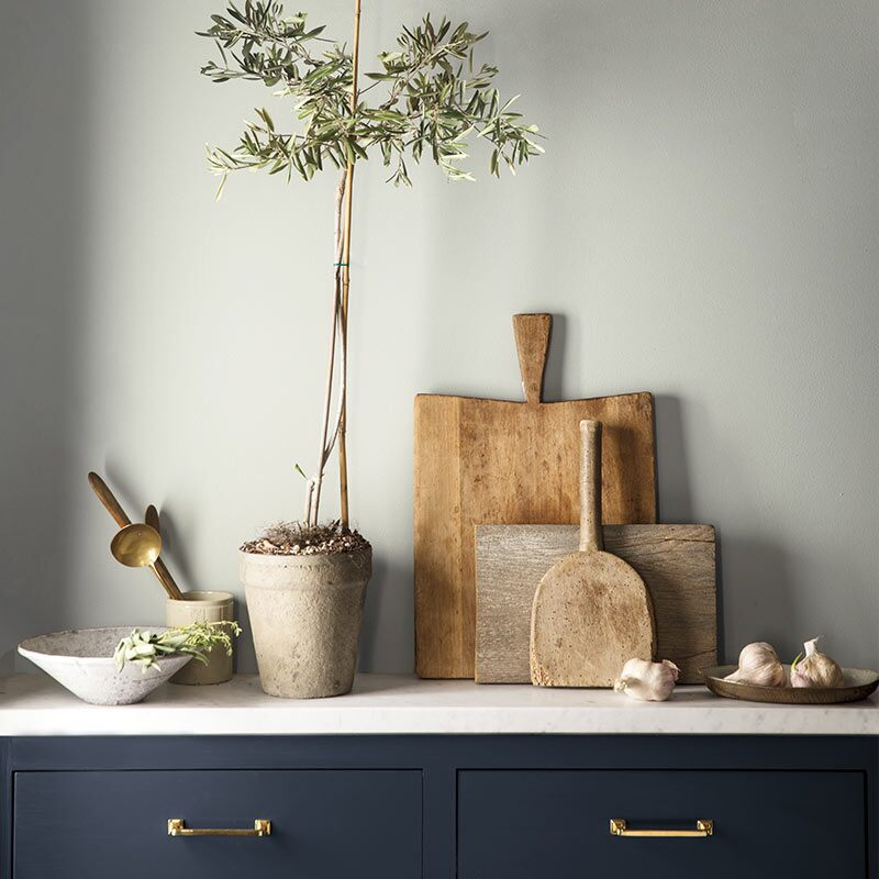 A navy-painted cabinet against a gray-painted wall features cutting boards and other kitchen items. Colour of the Year 2019