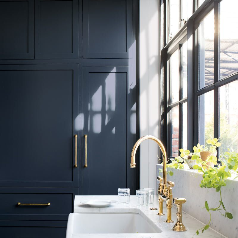 Navy-painted cabinets in a sleek kitchen with marble countertop, gold hardware and black trimmed windows. Colour of the Year 2019