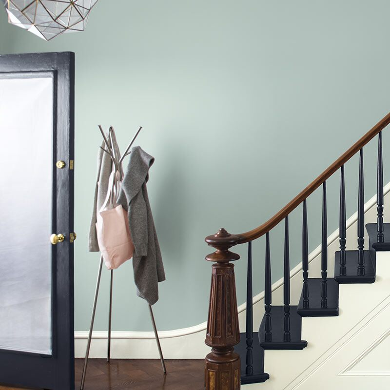 A blue-gray wall with white trim sets off a staircase with black stairs and an ornate wood banister. Colour of the Year 2019