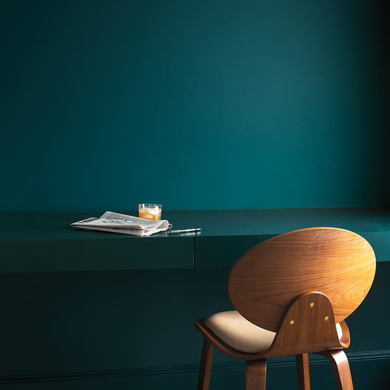 A rich teal wall with painted desk and armless wood chair. Colour of the Year 2019