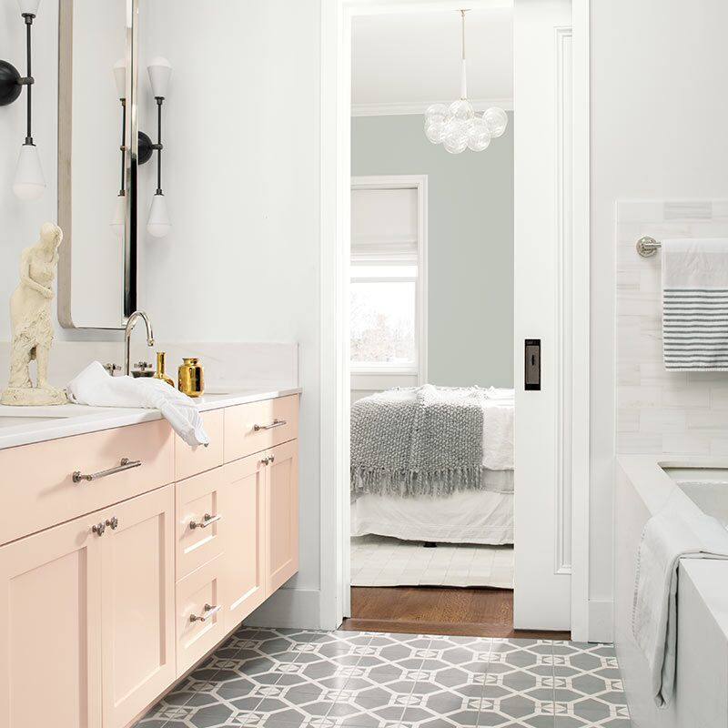 A white-painted bathroom with pale pink cabinets opens to a gray bedroom with contemporary chandelier. Colour of the Year 2019