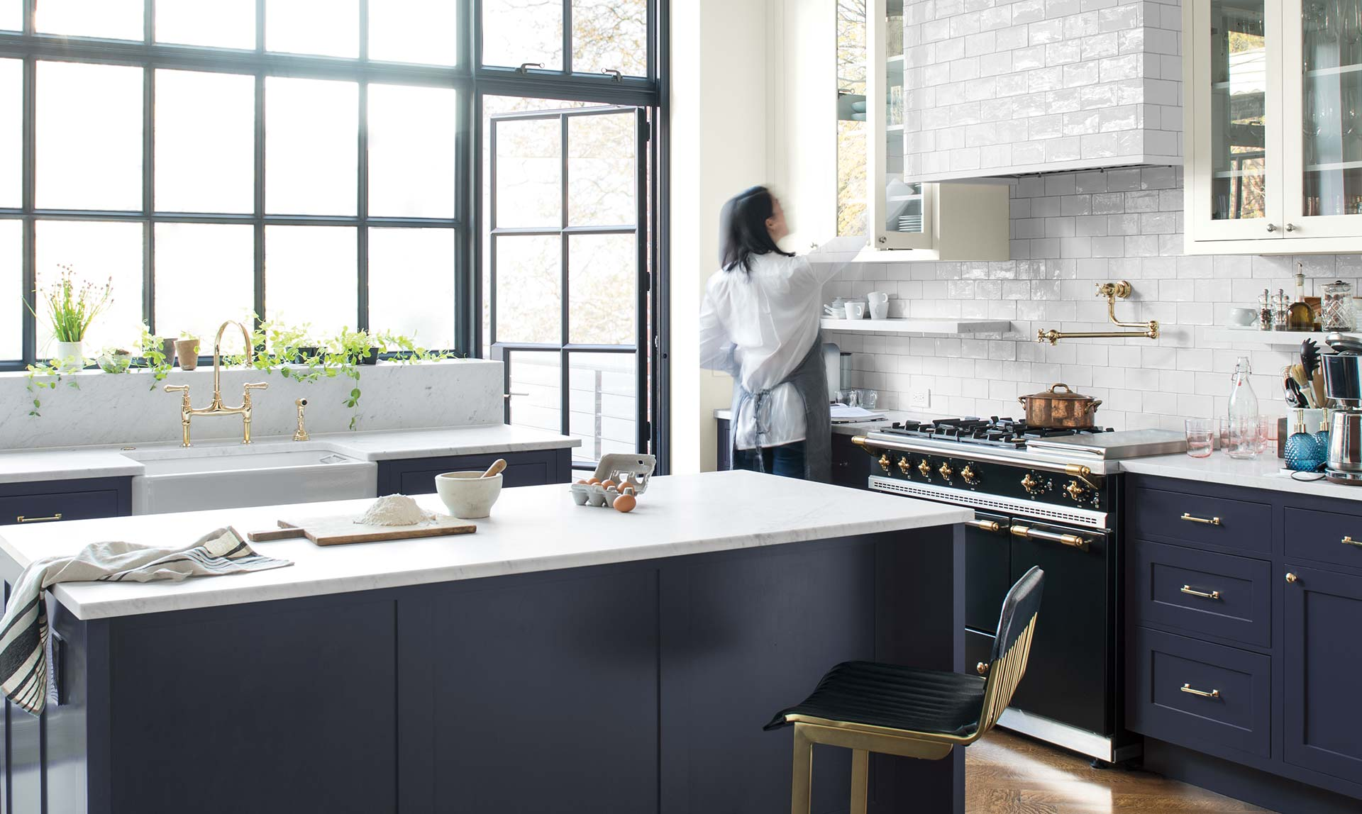 A woman reaches into a white-painted cabinet in an airy kitchen with a navy island. Color of the Year 2019