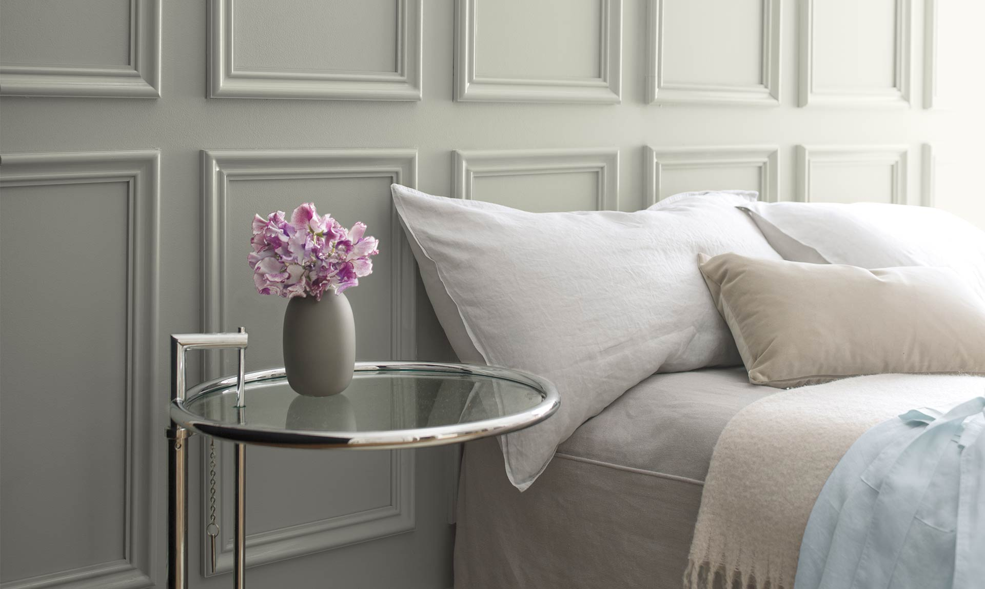 A bed against a gray wall with neutral-colored linens next to a glass side table. Color of the Year 2019