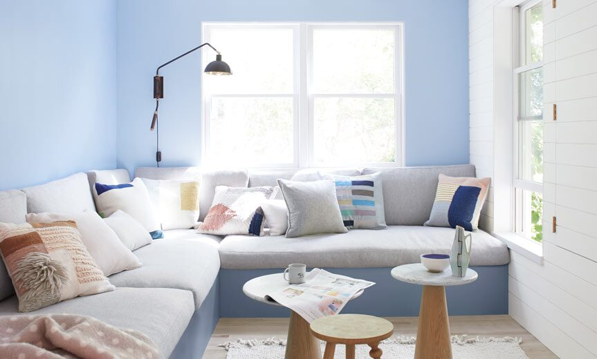 Light blue living room walls frame a large gray banquette