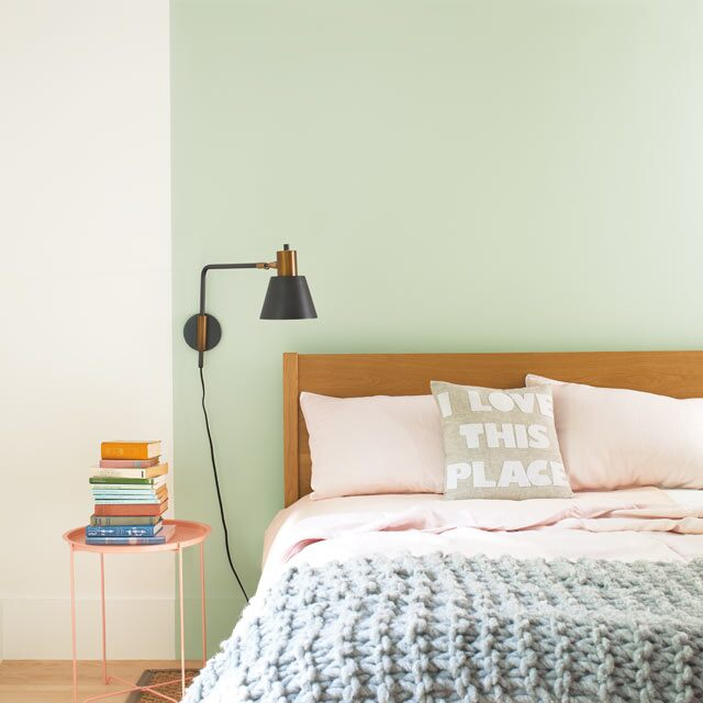 A bed set against a light green feature wall