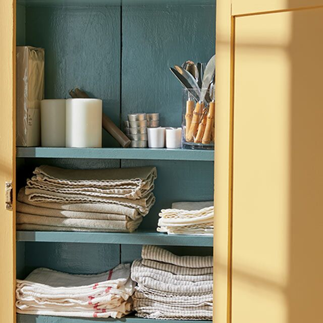 An open linen cabinet painted in Chestertown Buff HC-9 and Aegean Teal 2136-40.
