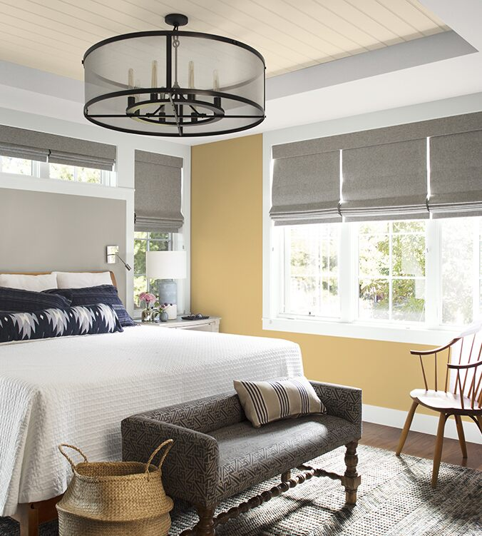 An airy bedroom with white bedding, navy and white pillows, circular chandelier, and upholstered bench.