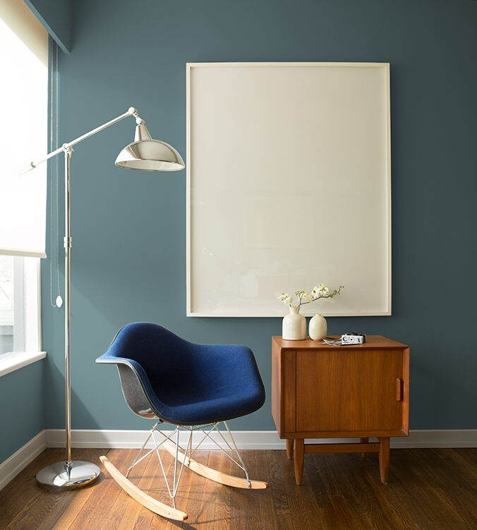Blue rocking chair, mid-century modern style side table, and contemporary chrome floor lamp in a cozy room corner.