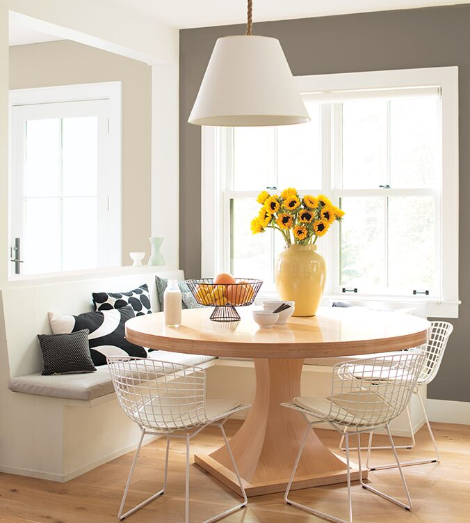 A light-filled dining area with built-in banquettes, round wood kitchen table, mesh white chairs and white pendant lamp.