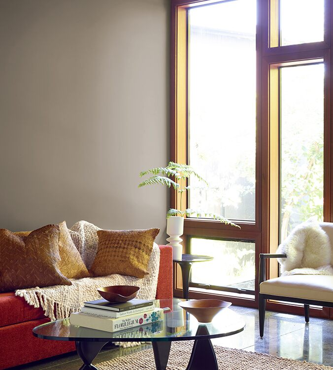 A contemporary den with floor-to-ceiling-windows, modern glass coffee table, and orange couch with cream colour throw.