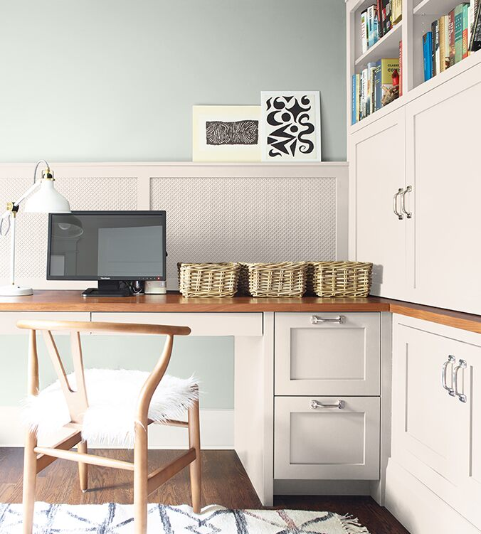 A corner office nook with built-in desk, cabinets and bookshelves, blond wood chair, and white desk lamp.