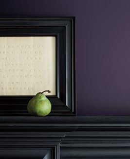 A wall painted in Shadow 2117-30 and a mantel in Ebony King 2132-20 with a green pear and white print in black frame.
