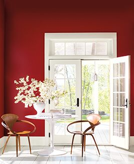A rich red sitting room is flooded with light through several white French doors.