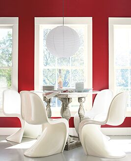 An intimate dining room with four white tulip chairs offers a view through large windows framed in white against a striking red dining room wall.