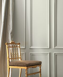 A gray-painted wall and cream-colored silk curtains frame a formal gold chair.