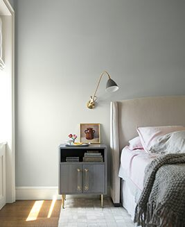 An airy bedroom with gray-painted walls and white trim features neutral bedding and metallic accents.