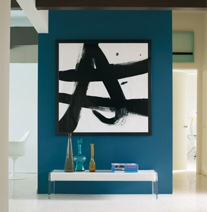 A bold blue accent wall offsets a black and white graphic painting in a bright hallway.