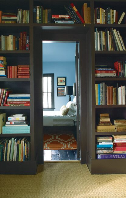 A doorway into a welcoming, blue-hued bedroom lit by natural light is framed by dark wood shelving featuring a large collection of books.