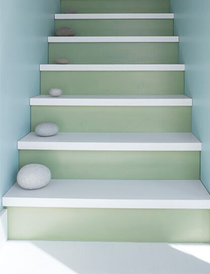Shades of blue, green and gray lead the way up a staircase accented by a series of round rocks on each step.