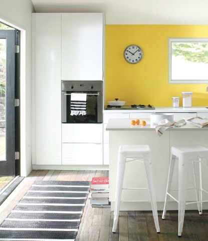 Trendy kitchen with yellow wall and industrial chairs