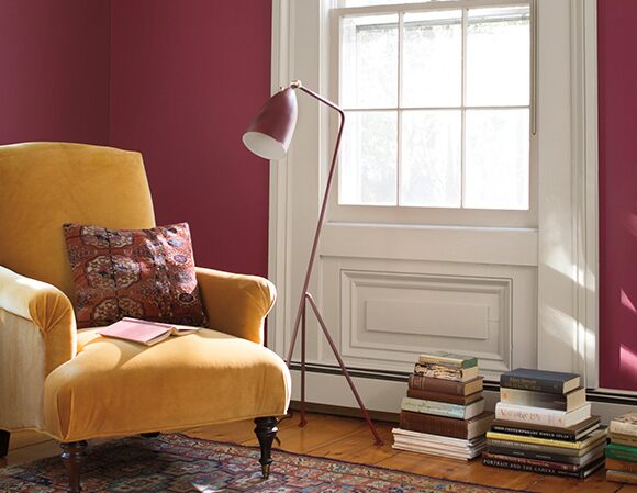 Magenta wall with yellow velvet chair