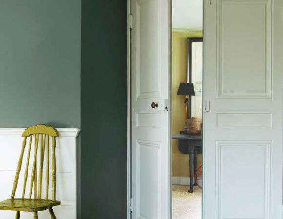 Light green accent chair along dark green wall
