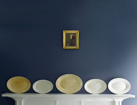 Deep blue accent wall with decorative plates against white mantel