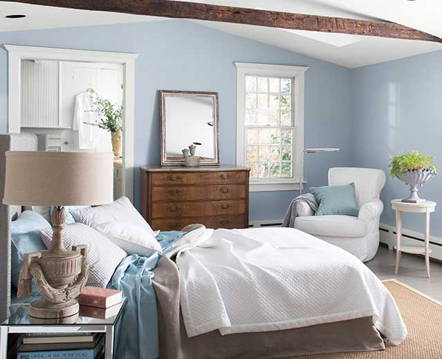 A bedroom with walls painted in Instinct AF-575, displaying the impact of cool paint colours.