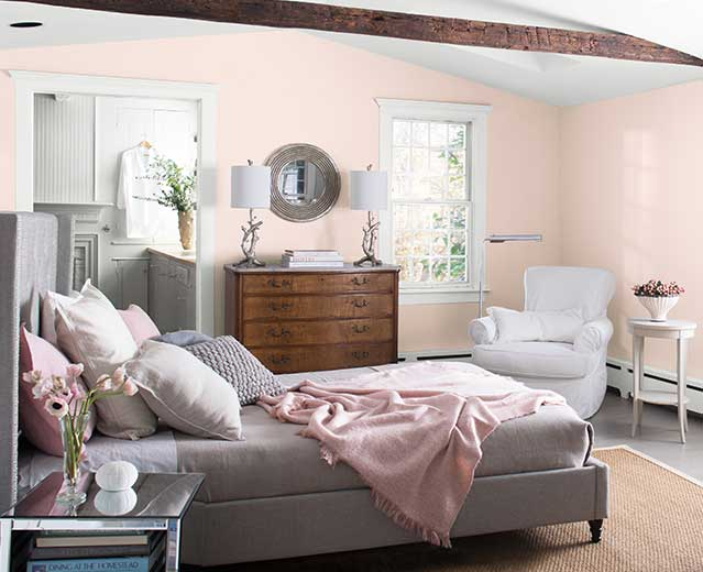 A bedroom with walls painted in Mellow Pink 2094-70, displaying the impact of warm paint colours.