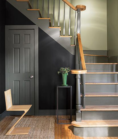 A dark blue-painted traditional entryway takes a twist with modern accents.