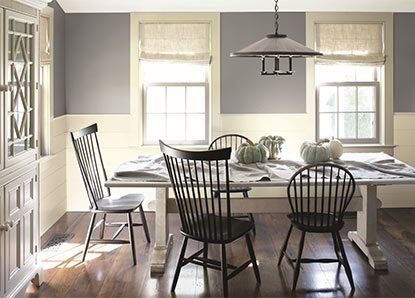 A pale gray-painted dining room, detailed with white wainscoting and black colonial-style chairs.