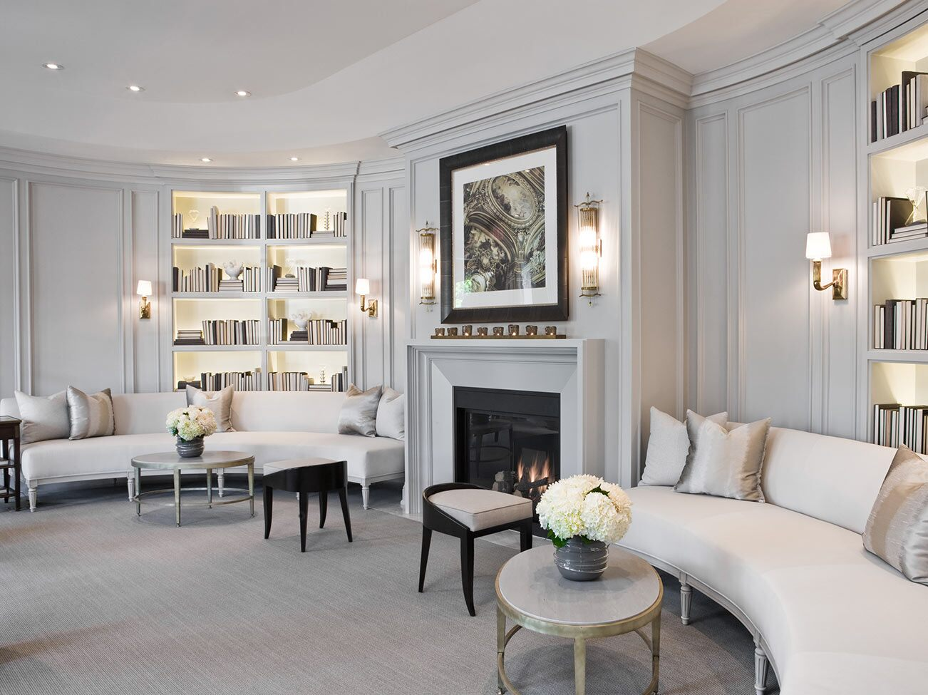 An elegant living room with wall sconces, two matching light gray sofas, and built-in bookcases on each side of a gray fireplace.