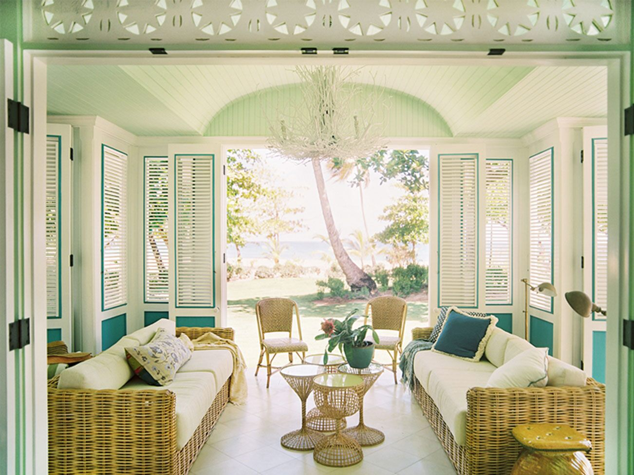 An island veranda in green and creamy white hues with hinged shutter panels, two woven wicker sofas and matching chairs.