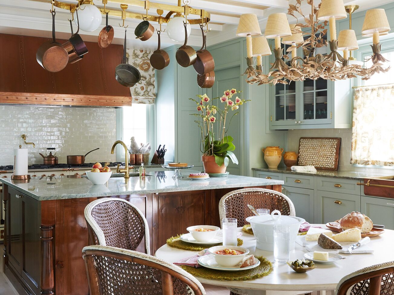 Beamed ceiling kitchen with copper range hood, large wood base island, and elegant small table with French bistro chairs.