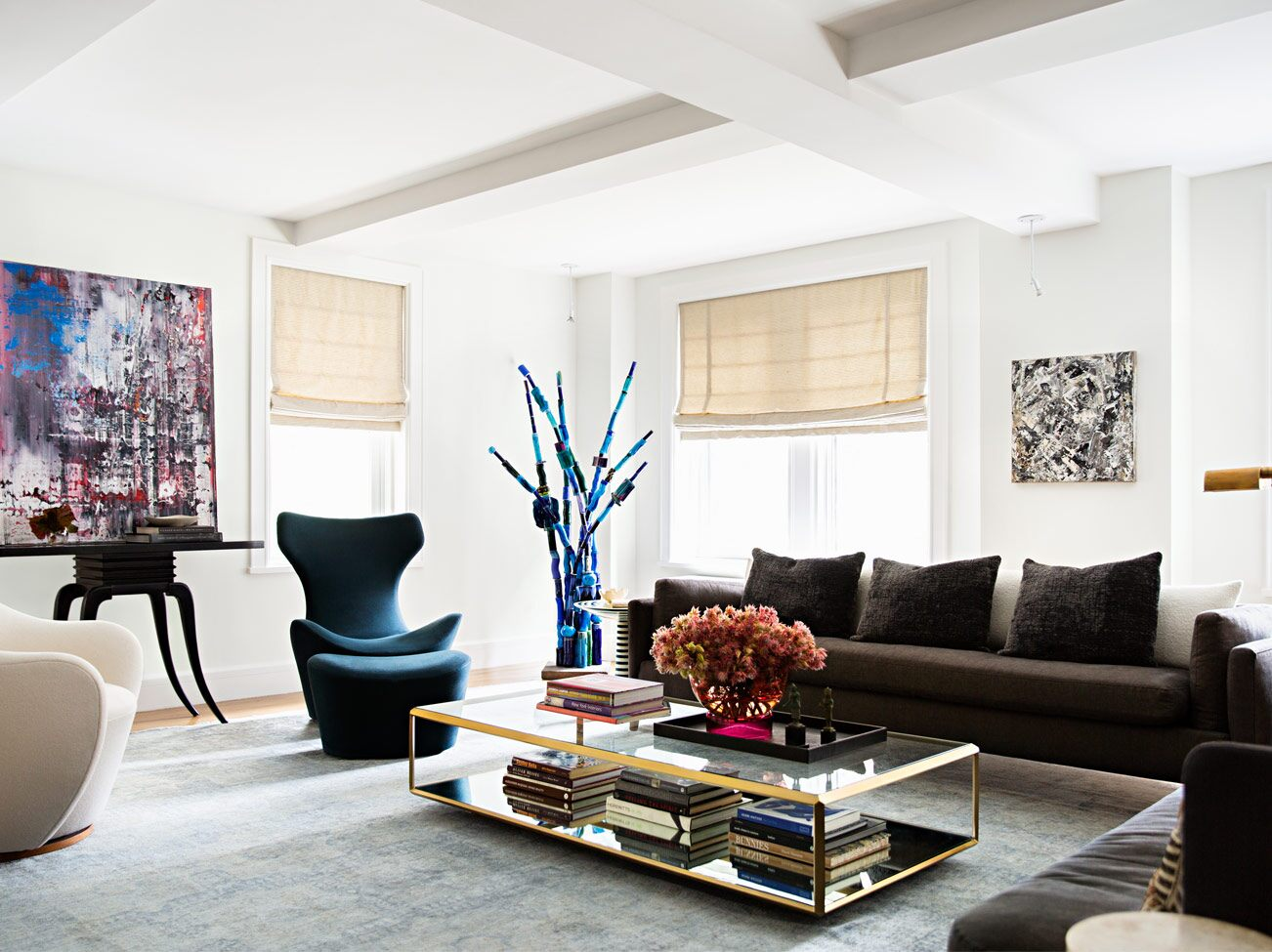 White-painted living room with coffered ceiling, brown sofa, modern chairs, gold-framed glass coffee table & abstract art.