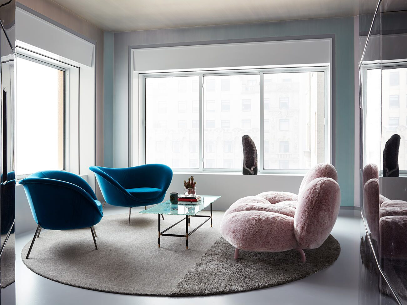 Corner sitting room with windows, light blue painted walls, contemporary furniture, natural light, and circular rug.