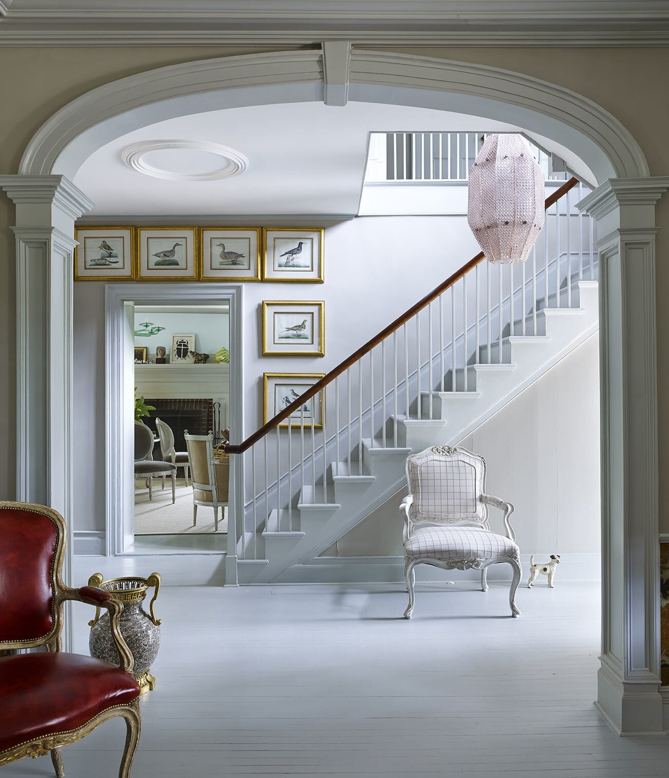 Elegant staircase viewed through ornamental arch with framed walls prints at base of stairs.