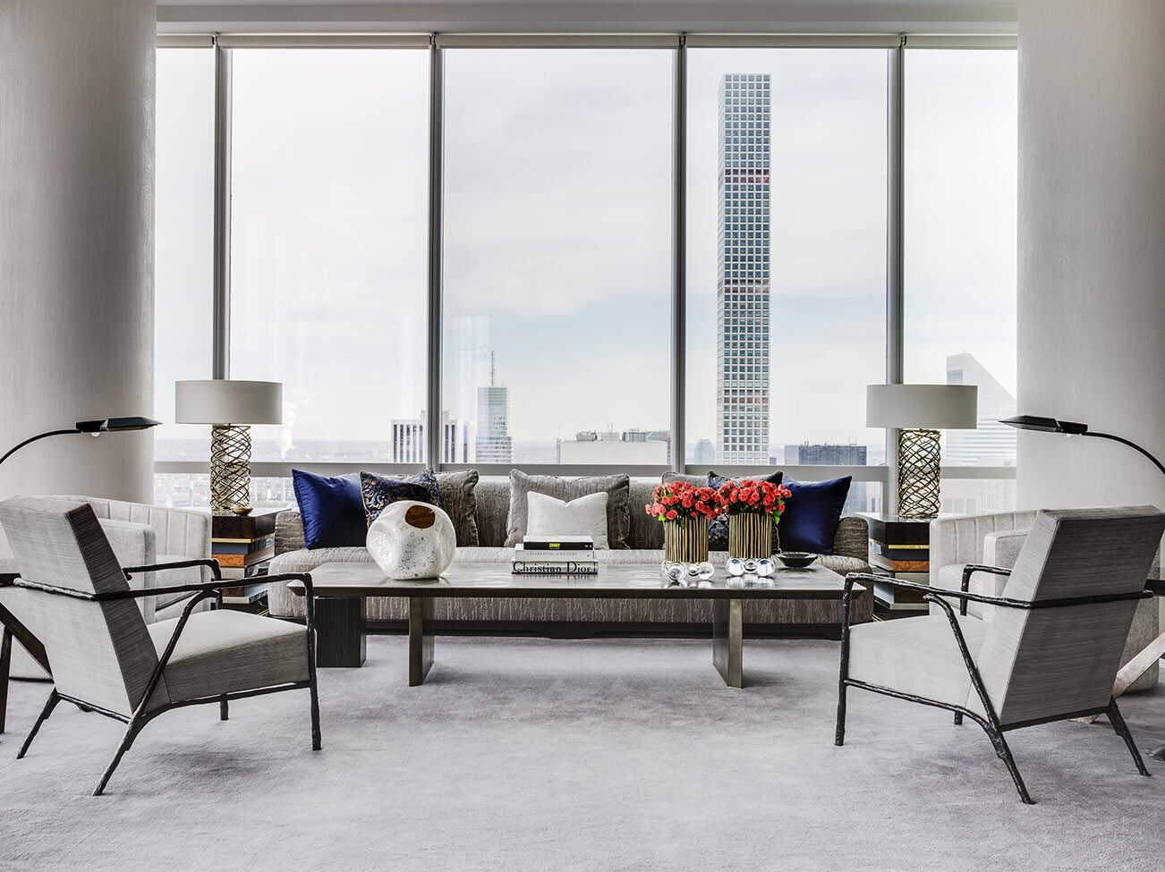 A sleek, white-painted living space with modern furnishings and massive floor to ceiling windows overlooks a cityscape.