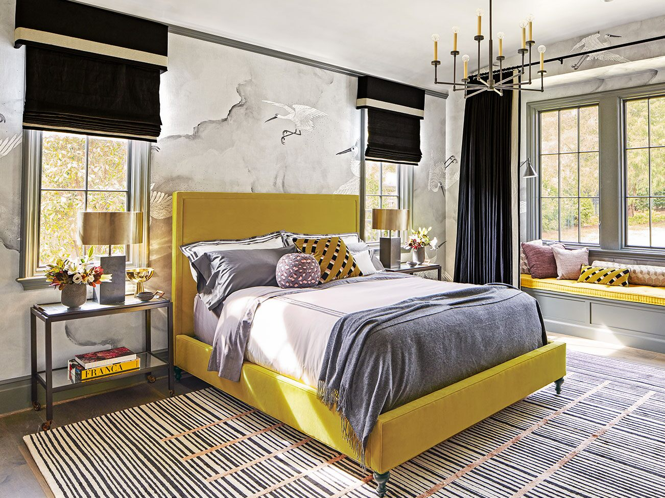Bedroom with cloud mural, black window treatments, striped area rug, mustard yellow upholstered bed and window seat.