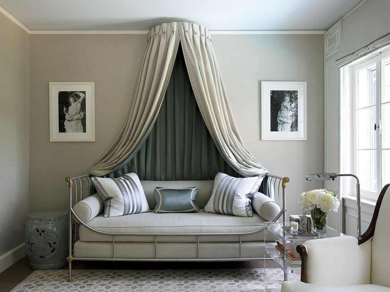 Sitting room in neutral tones with sky blue-painted ceiling, cushioned day bed with draped canopy, and striped pillows.