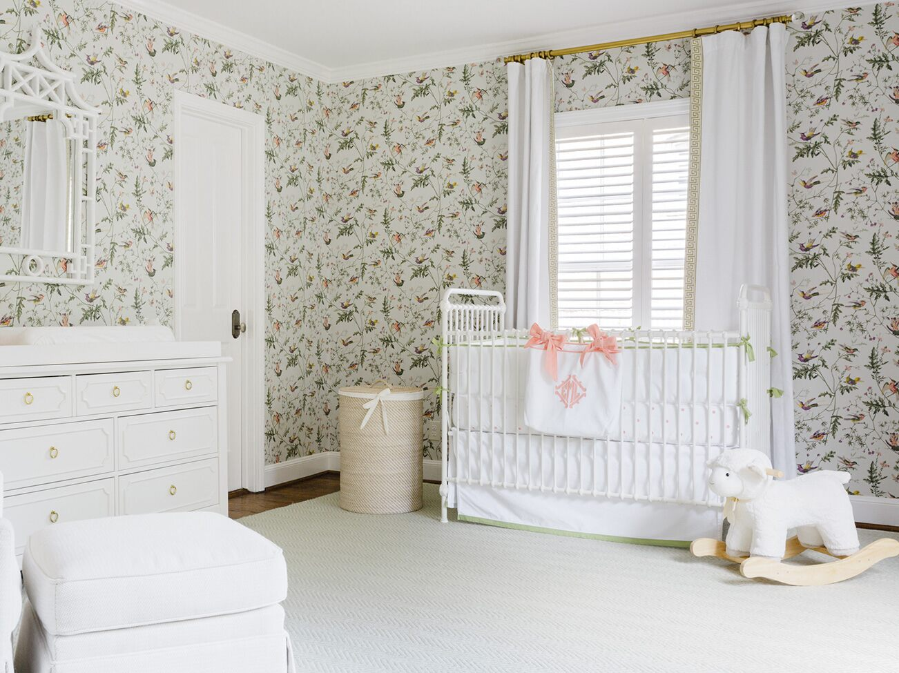 Cheery floral-papered nursery with floor-to-ceiling white drapes, white crib, dresser, chair, and white plush baby rocker.