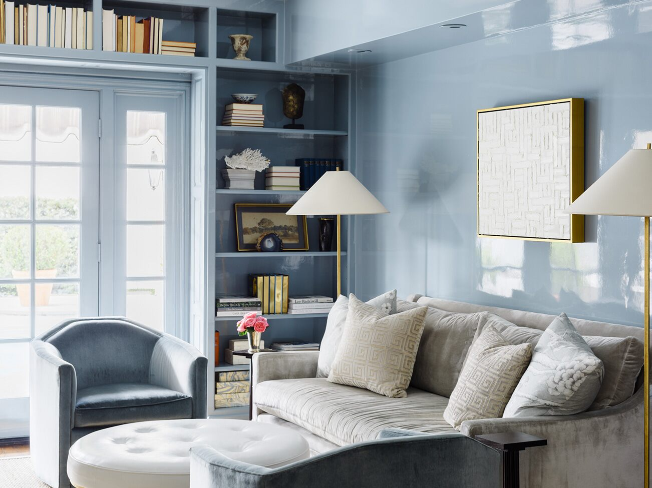 A pale blue, high gloss-painted study, gray couch, white leather ottoman, blue chairs, and a light-filled French door.