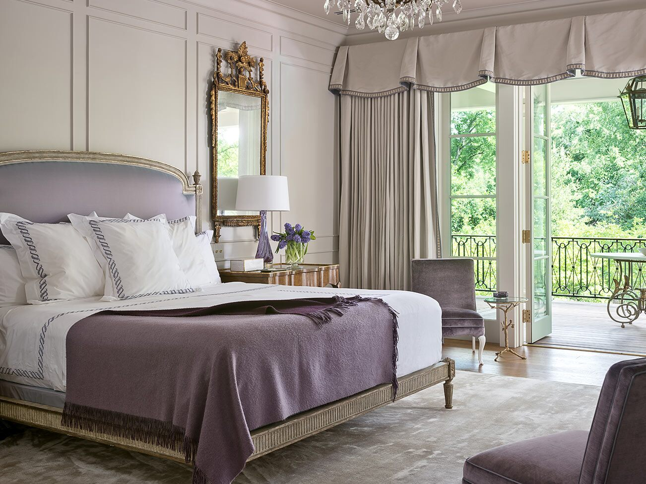 Glamourous light gray and pale lavender bedroom, paneled walls, large king bed, draped windows and door open to terrace.
