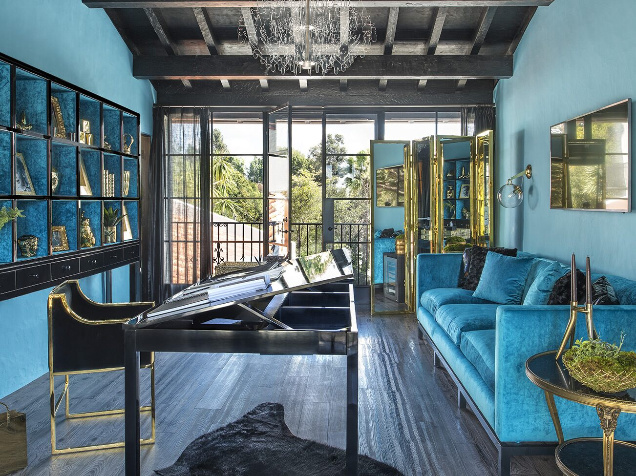 Turquoise-painted room with black beamed ceiling, blue tuxedo sofa, ebony tilt top desk, and doors opening to an exterior view.