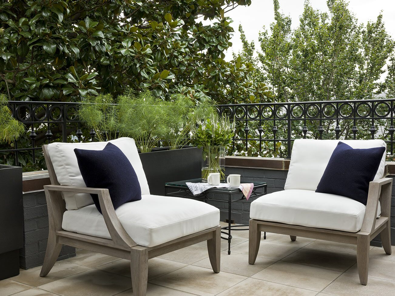 Stone patio with decorative wrought iron railing, white cushioned chairs, and navy accent pillows set against lush greenery.