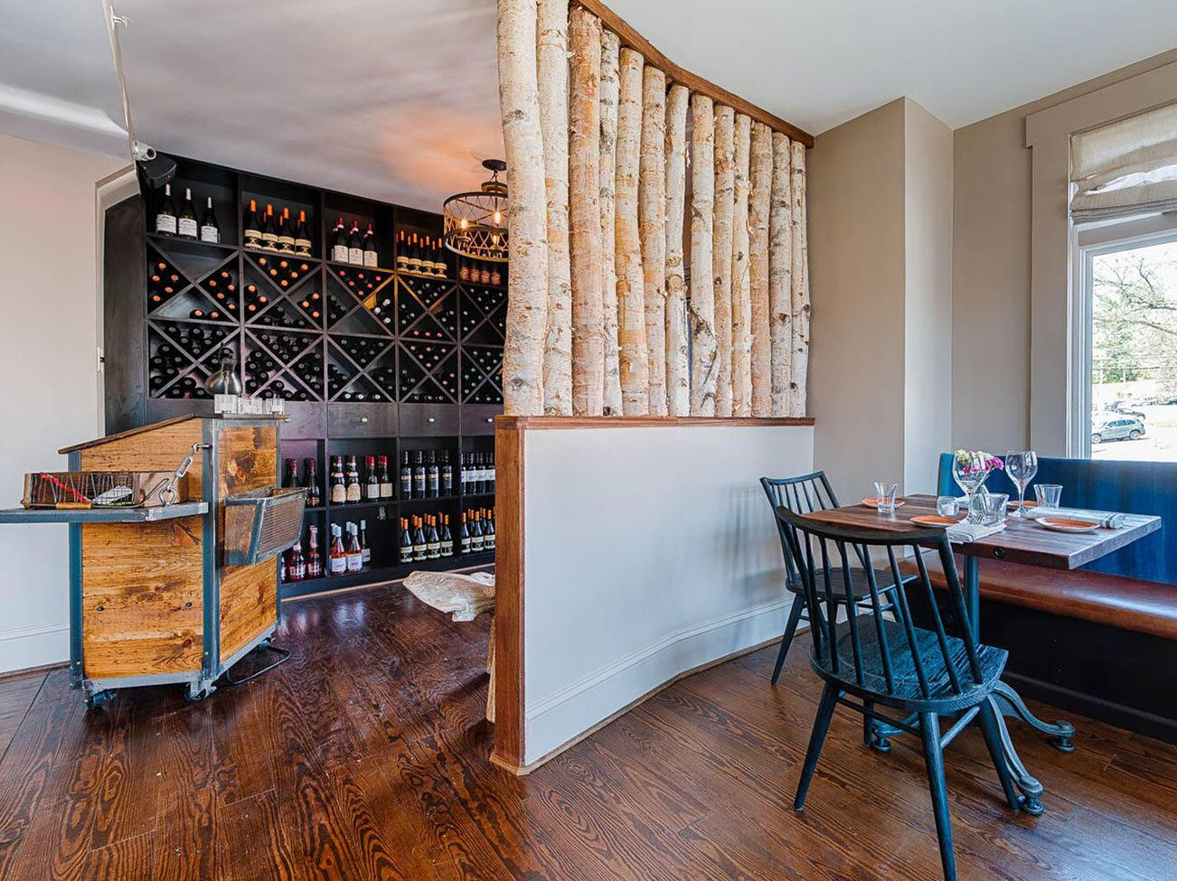 A wine room and office area, separated by a small curved wall, wood floor, and blue-painted chairs.