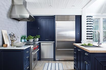 Sunny, modern kitchen with blue cabinetry and stainless steel appliances