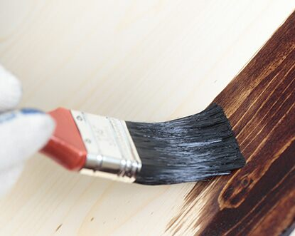Paint brush applying wood stain