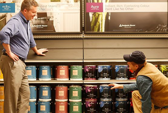 A contractor interacts with staff in a Benjamin Moore store