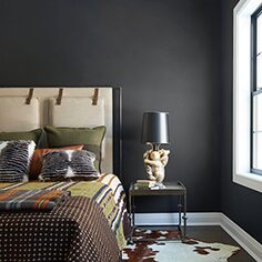 Black bedroom walls with a white and brown cow print rug underneath a tan bed with a printed comforter.